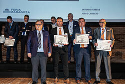 Entrega de premios con cuatro hombres y diplomas en primera fila