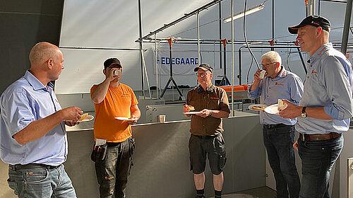 Cinco hombres comen y beben mientras conversan.